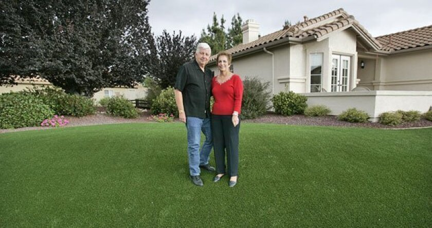 David and Rosie Lang of Alpine recently replaced a hard-to-maintain natural lawn with an artificial one. David, a retired city water employee, plans to get rid of his lawn mower. (Peggy Peattie / Union-Tribune)