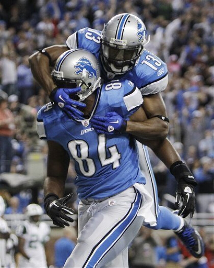 Detroit Lions tight end Brandon Pettigrew (84) celebrates his 10-yard touchdown reception against the New York Jets as wide receiver Nate Burleson jumps onto him in the first quarter of an NFL football game in Detroit on Sunday, Nov. 7, 2010. (AP Photo/Paul Sancya)