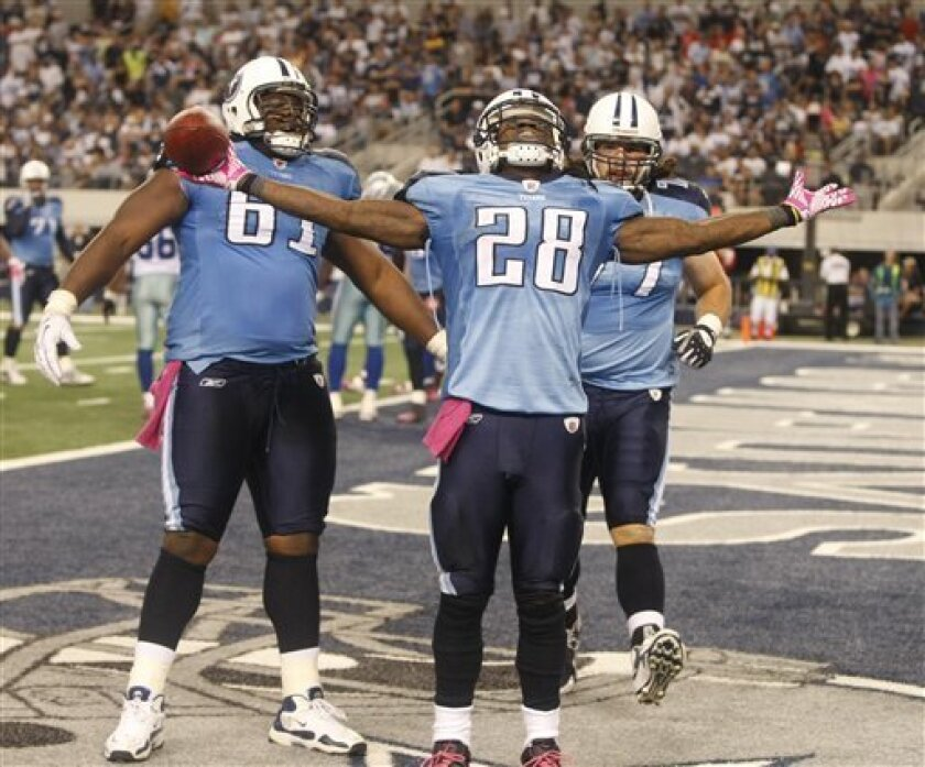 Tennessee Titans running back Chris Johnson (28) celebrates his touchdown with teammates Fernando Velasco, left, and Ryan Durand (77) during the second half of an NFL football game against the Dallas Cowboys on Sunday, Oct. 10, 2010, in Arlington, Texas. (AP PhotoWaco Tribune-Herald, Jose Yau)
