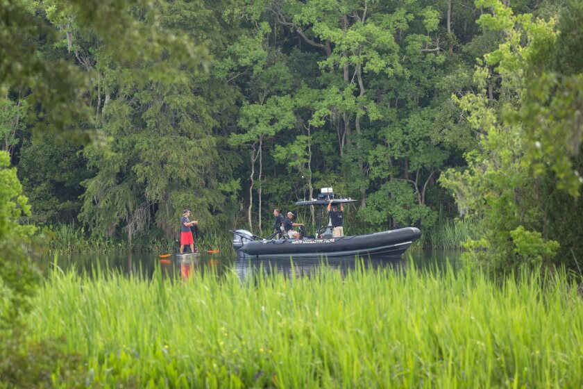 North Charleston police assist in a water search in a residential area where a U.S. Air Force F-16 fighter aircraft collided with a small private airplane near Moncks Corner, S.C., on Tuesday.
