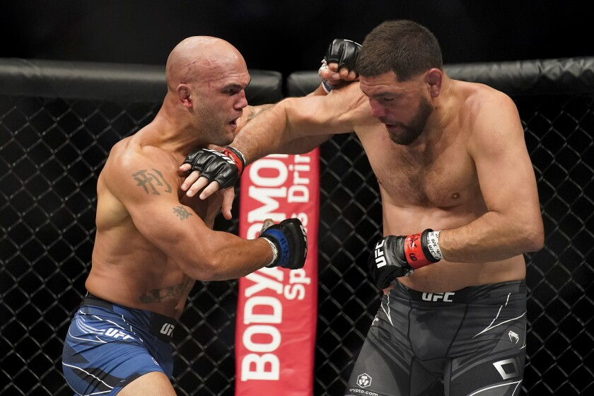 Robbie Lawler, left, throws a punch against Nick Diaz during a middleweight.
