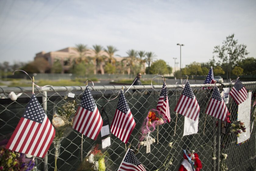 A security guard patrols the empty parking lot of the Inland Regional Center in San Bernardino, the site of a Dec. 2 massacre by Syed Farook and Tashfeen Malik. The perimeter fence of the center is covered with memorial items on Dec. 21.
