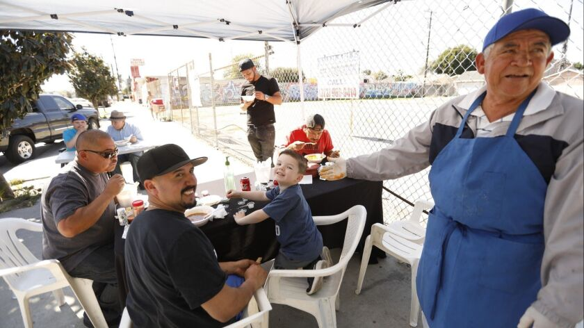COMPTON, CA - MARCH 17, 2019 ? Joel Mendez, right, enjoys a light moment with customers at his Mr. M
