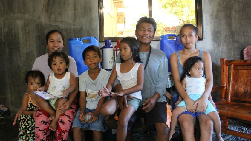 Efren Forones with his family. Left to right: A neighbor's unidentified child; Leah, 25, with her son Jaren, 2, in her lap; Emmanuel, 10; Emmaglyn, 5, on Forones' knee; Sheila, 22, with her daughter, 1-year-old Villagail, in her lap.