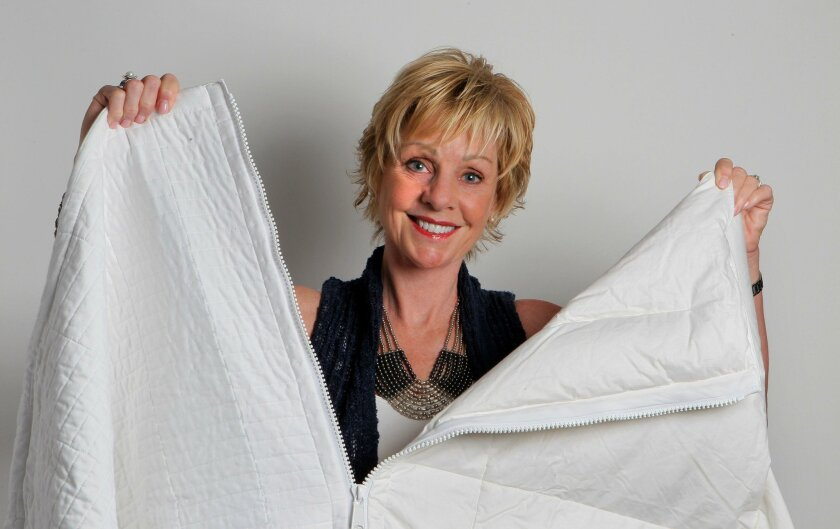 October 27, 2015_Oceanside, California_USA_| Portrait of Renae Farley, CEO of Keep The Peace Bedding, holding one of her company's bedding products with its zipper separating it with two different materials. |_Mandatory Photo Credit: Photo by Charlie Neuman/San Diego Union-Tribune/©2015 San Diego U