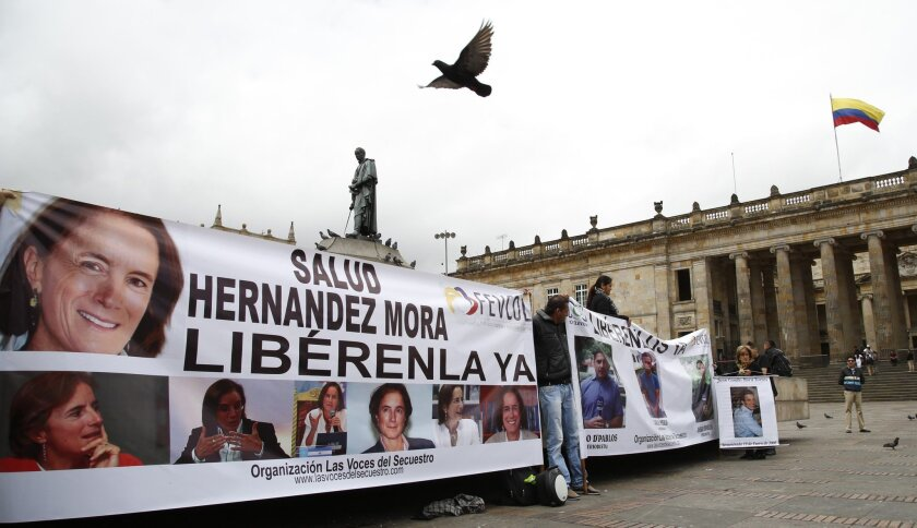 Demonstrators hold banners asking for the release of three journalists who are believe to have been taken hostage, during a sit-in in Bogota, Colombia, Wednesday, May 25, 2016. Salud Hernandez-Mora, correspondent in Colombia for Spain's El Mundo and columnist for the Bogota daily El Tiempo, as well