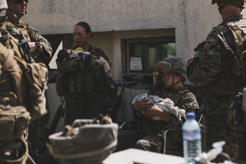 Marine Sgt. Nicole Gee and another U.S. service member hold Afghan babies.