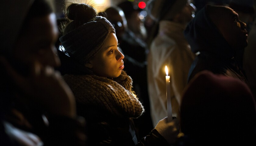 Mourners gather in New York at a candlelight vigil for NYPD Officers Wenjian Liu and Rafael Ramos.