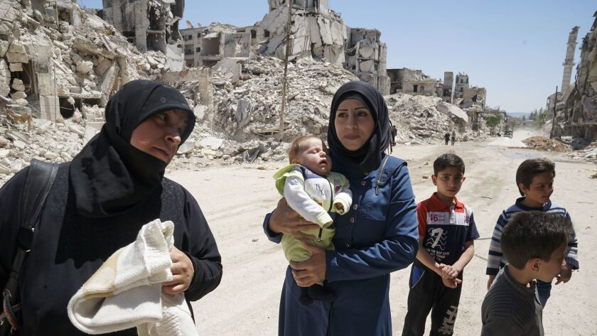 Sabah Sheikh Ali, 29, holds her 2-month-old son Taim, accompanied by her mother-in-law Souad Rasheed