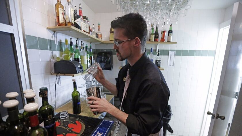 Dustin Humes fixes a drink out of the view of patrons at Vivace Restaurant in Salt Lake City, in keeping with one of Utah's strict laws on alcohol.