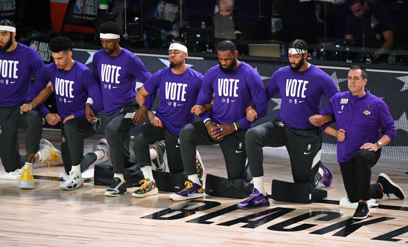The Lakers take a knee during the national anthem before Game 1 of the NBA Finals.