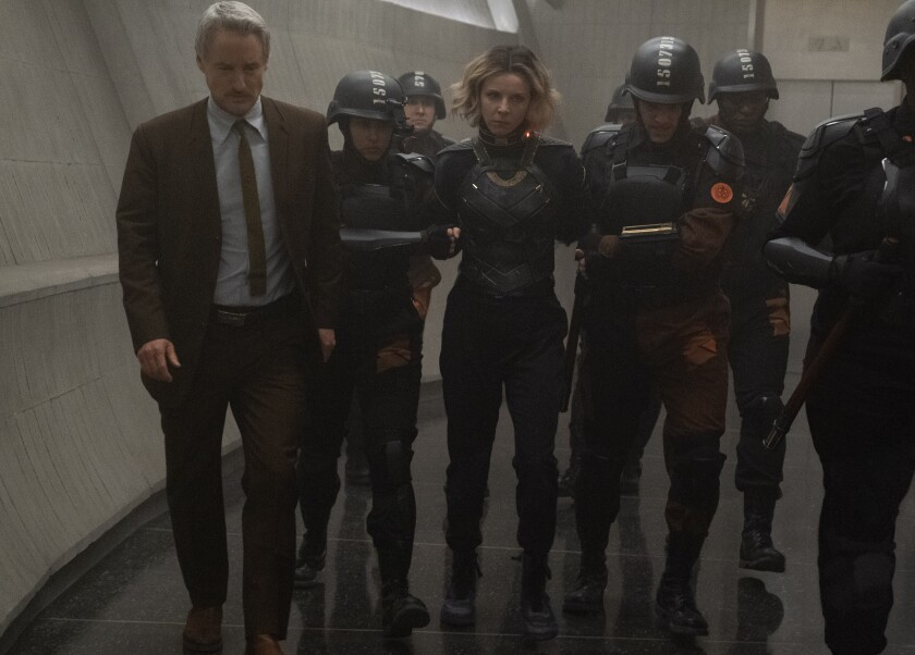 A man in a suit leads an armed escort of a woman prisoner