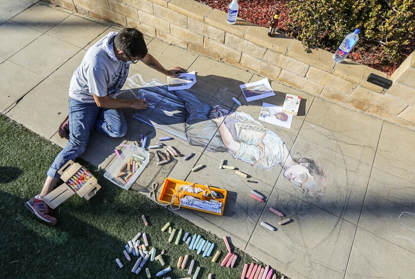 Artist Erick Toussaint works on one of his chalk art creations outside his Ocean Beach home.