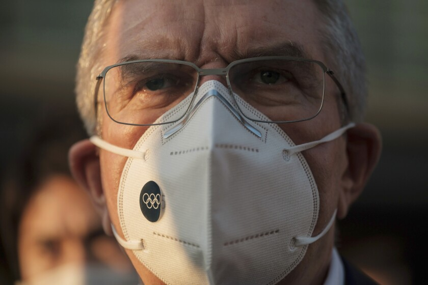 """IOC President Thomas Bach wearing a protective mask talks to journalists during a visit to Olympic and Paralympic Village in Tokyo Tuesday, Nov. 17, 2020. Bach said during this week's trip to Tokyo that he is """"encouraging"""" all Olympic """"participants"""" and fans to be vaccinated - if one becomes available - if they are going to attend next year's Tokyo Olympics. (Nicolas Datiche/Pool Photo via AP)"""