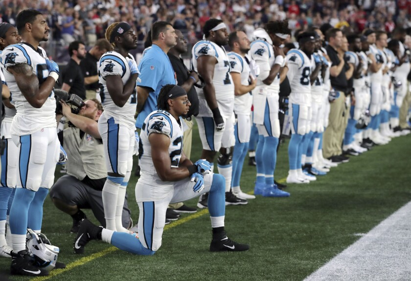 "FILE - In this Aug. 22, 2019, file photo, Carolina Panthers strong safety Eric Reid (25) kneels during the national anthem before the team's NFL preseason football game against the New England Patriots in Foxborough, Mass. Despite setting two defensive franchise records for the Panthers last season, Reid remains unsigned like his close friend Colin Kaepernick. Washington coach Ron Rivera, Reid's former coach in Carolina, gave him a strong endorsement Wednesday, Sept. 16. ""I would tell them he's a heckuva teammate,"" Rivera said. ""He came in and the young man did exactly what was asked of him."" (AP Photo/Charles Krupa, File)"