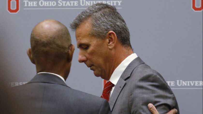 Ohio State President Michael Drake speaks with football coach Urban Meyer as he leaves a news conference Wednesday in Columbus, Ohio. Meyer was suspended three games for mishandling domestic-abuse allegations involving a member of his coaching staff.