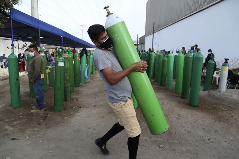 Un hombre carga una botella vacía de oxígeno para rellenarla tras hacer fila en la Villa El Salvador de Lima, el jueves 18 de febrero de 2021. Países de África y América Latina sufren una crisis de suministro de oxígeno médico para los pacientes de coronavirus, después de que se ignorasen las advertencias al respecto al inicio de la pandemia. Los médicos dicen que la escasez ha provocado muertes innecesarias. (AP Foto/Martin Mejia)
