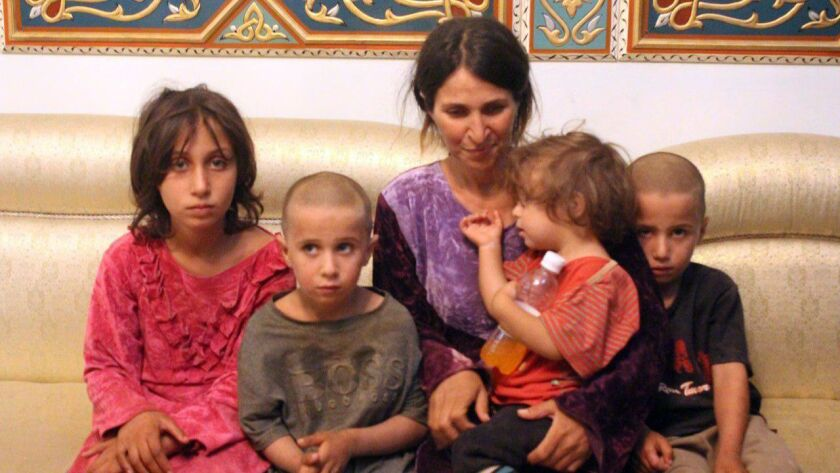 A handout picture released by the Syrian Arab News Agency shows a woman and four children who were among six released Oct. 20, 2018, by the Islamic State group in a prisoner swap with the Syrian government and ransom, in Syria's southern city of Sweida.