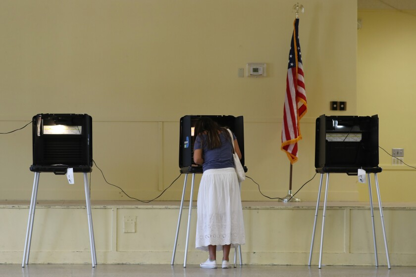 Gissele Riberiro fills out her ballot as she votes at the Legion Park.