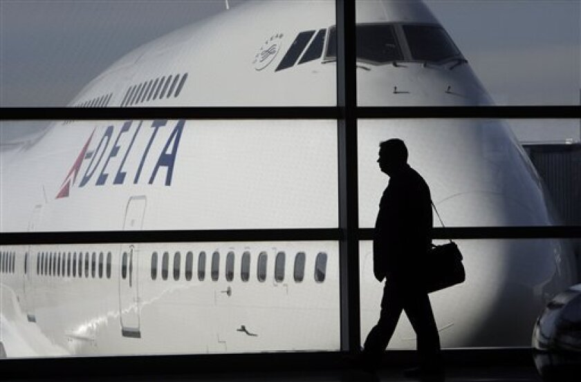 FILE - In this photo made Jan. 21, 2010, a passenger walks past a Delta Air Lines 747 aircraft in McNamara Terminal at Detroit Metropolitan Wayne County Airport in Romulus, Mich. Delta Air Lines Inc. said Thursday, June 11, 2010, it plans to offer first-class seats on all domestic flights longer than 750 miles _ about two and a half hours _ beginning this fall. (AP Photo/Paul Sancya, file)