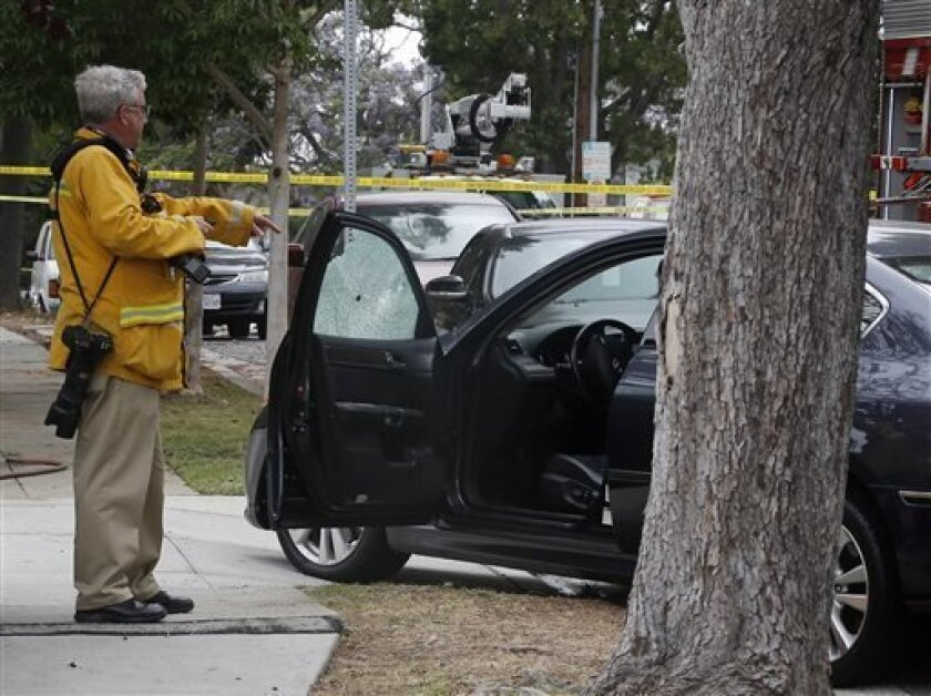 An investigator checks a car damaged by a bullet at the intersection of Kansas and Yorkshire about a mile northeast of Santa Monica College in Santa Monica, Calif. on Friday, June 7, 2013. (AP Photo/Reed Saxon)