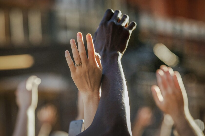 FILE - This photo from Sunday May 31, 2020, shows demonstrators raising their hands during a rally in Brooklyn, N.Y., for George Floyd, a black man who died in Minneapolis after being restrained by police officers. The chaos unleashed in 2020, amid the coronavirus pandemic, has created space for different voices to speak, for different conversations to be had and for different questions to be asked. (AP Photo/Kevin Hagen, File)