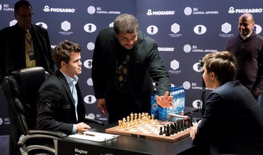 El astrofísico estadounidense Neil deGrasse Tyson (c), realiza el primer movimiento para el jugador noruego Magnus Carlsen (i), campeón mundial de ajedrez, ante el aspirante, el ruso Sergey Karjakin (d), durante la octava partida del Campeonato del Mundo de Ajedrez en Nueva York, Estados Unidos, el 21 de noviembre de 2016. EFE/Archivo
