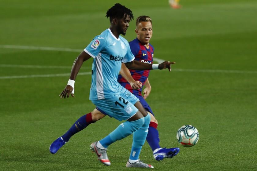 Chidozie Awaziem (primer plano) del Leganés pugna un balón con Arthur Melo del Barcelona en un partido de la Liga de España, el martes 16 de junio de 2020. (AP Foto/Joan Montfort)