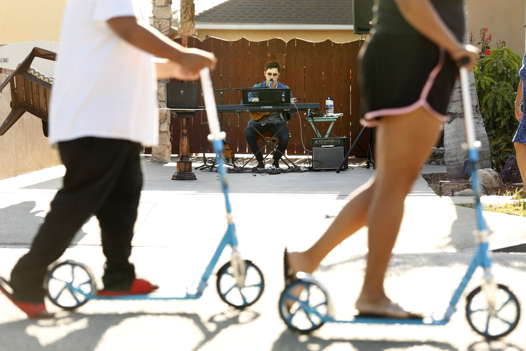 Andres O'Neil, 18, performs music in his driveway at home in Norwalk, California.