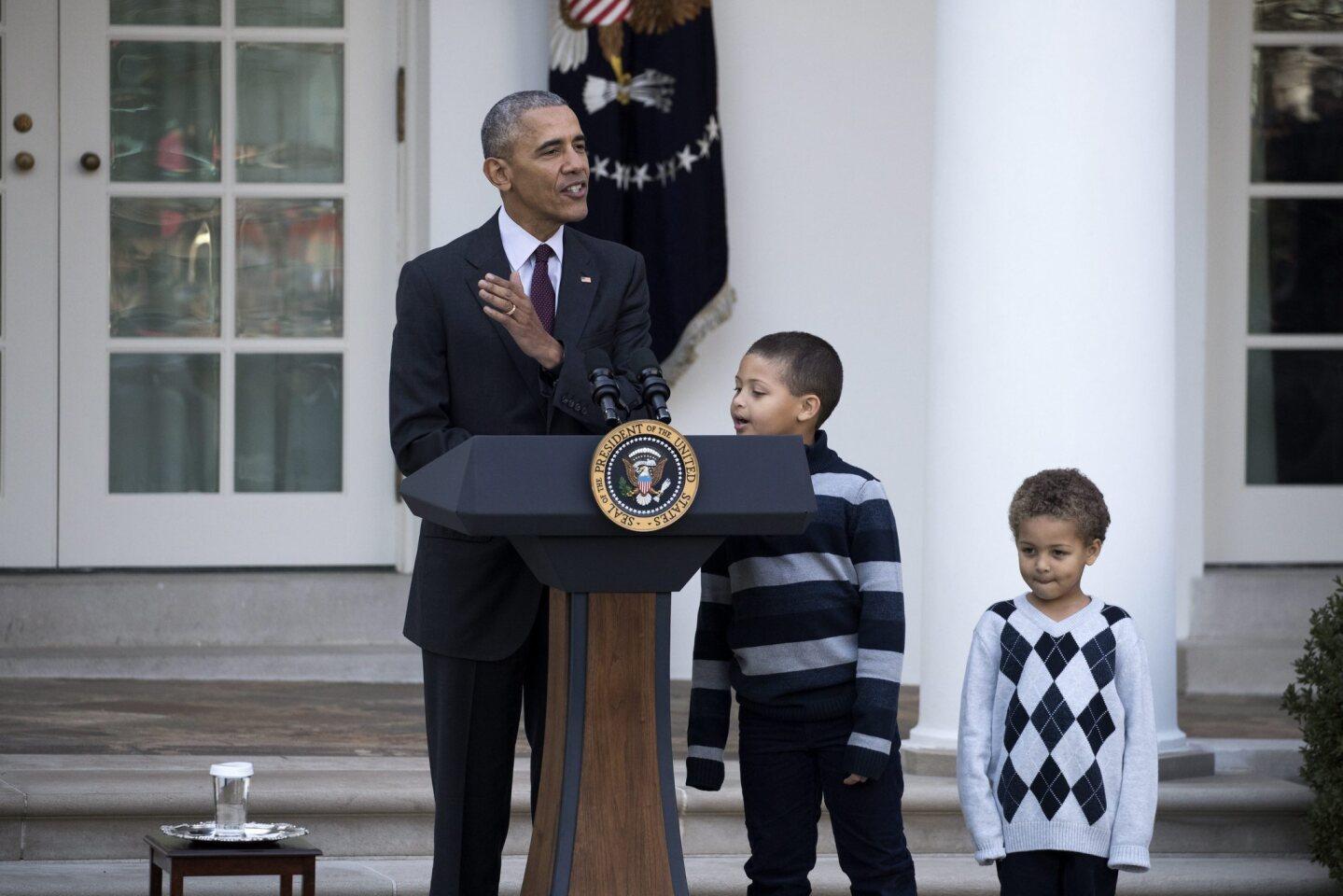 El presidente de Estados Unidos, Barack Obama (i), acompañado de sus sobrinos Austin (c) y Aaron Rbinson (d), ofrece un discurso tras perdonar a 'Tater', el pavo nacional del Día de Acción de Gracias, en el Jardín de las Rosas de la Casa Blanca en Washington.