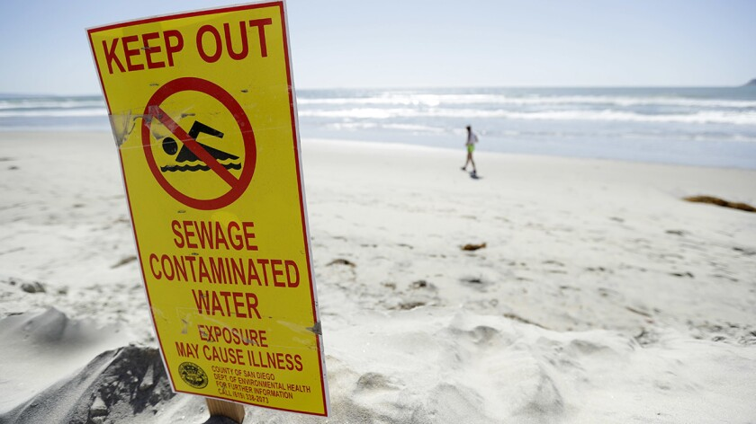 A sign warned of sewage-contaminated ocean waters in March on a beach in Coronado.