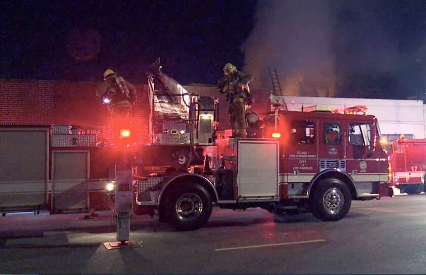 In the early morning, fire trucks are parked outside a fire in Boyle Heights, with a ladder extended over a roof.
