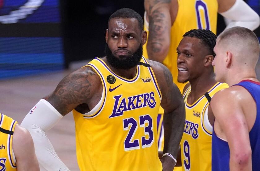 Lakers star LeBron James stands next to teammate Rajon Rondo, center, and Denver's Nikola Jokic.