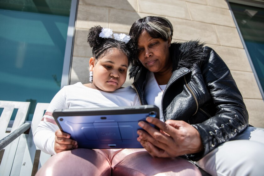 Glenda Evans works through a school assignment on a tablet with her 8-year-old granddaughter, Heavenly.