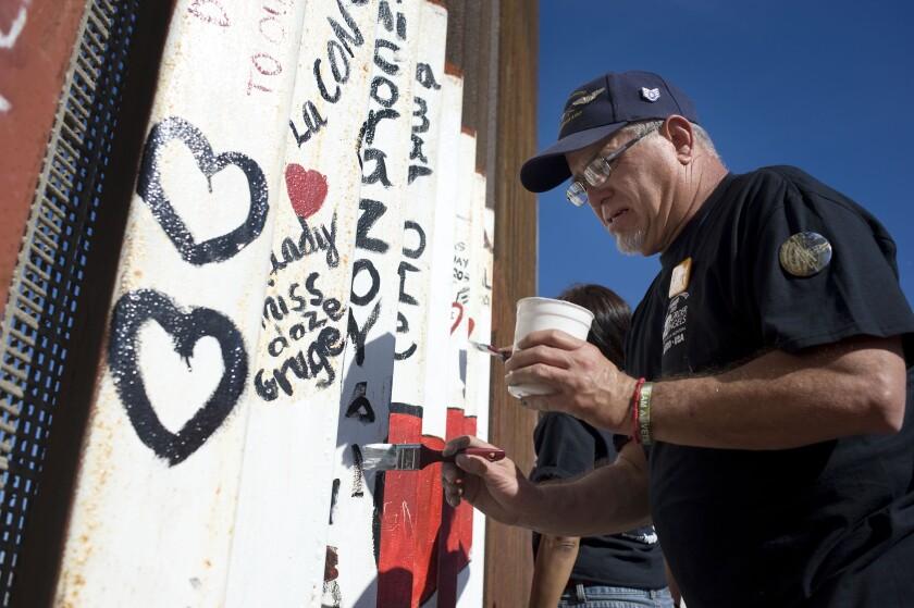Robert Vivar helps paint part of the U.S.-Mexico border wall.