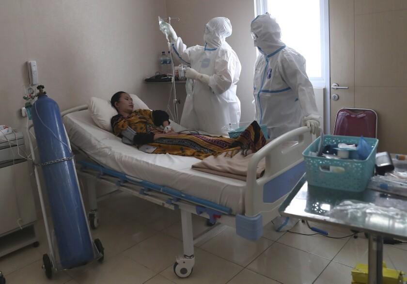 Trabajadores de la salud atienden a un enfermo con COVID-19 en el Hospital General Dr. Suyoto en Yakarta, Indonesia