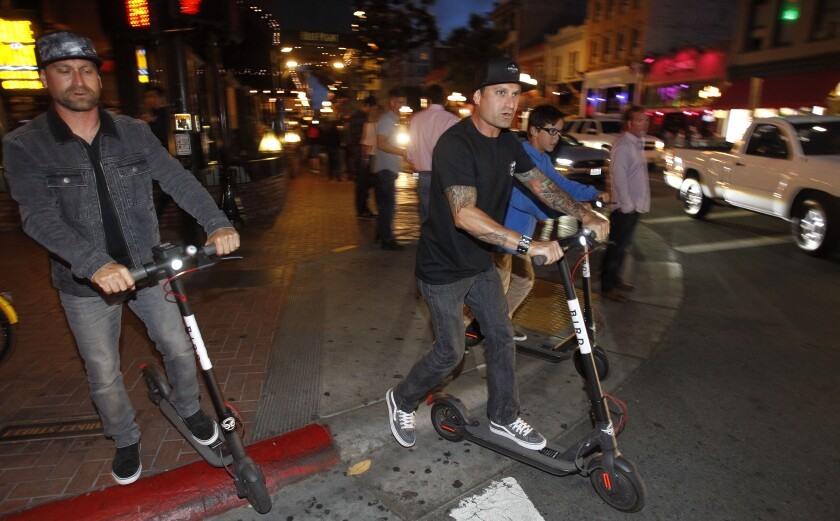 Dominick Ucello, left, and his brother Anthony Ucello  ride electric scooters in Gaslamp Quarter in San Diego on Friday, May 25, 2018.