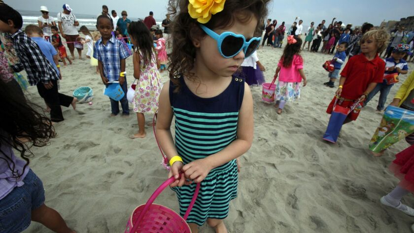 Juliana Cartwright, 4, searches for any remaining eggs in case one of the other 50 kids might have missed one, during the Easter egg hunt Sunday at Belmont Park.