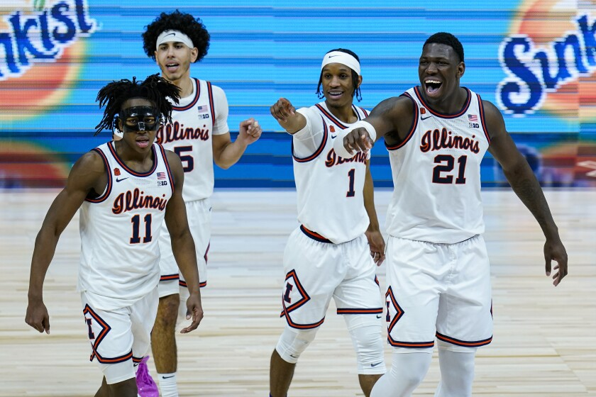 Illinois players Ayo Dosunmu (11), Andre Curbelo (5), Trent Frazier (1), and Kofi Cockburn (21) wave to fans in the closing minute of overtime in an NCAA college basketball championship game at the Big Ten Conference tournament, Sunday, March 14, 2021, in Indianapolis. Illinois defeated Ohio State in overtime(AP Photo/Michael Conroy)