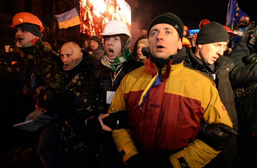 Protesters defend their barricades in front of riot policemen on Independence Square in Kiev.