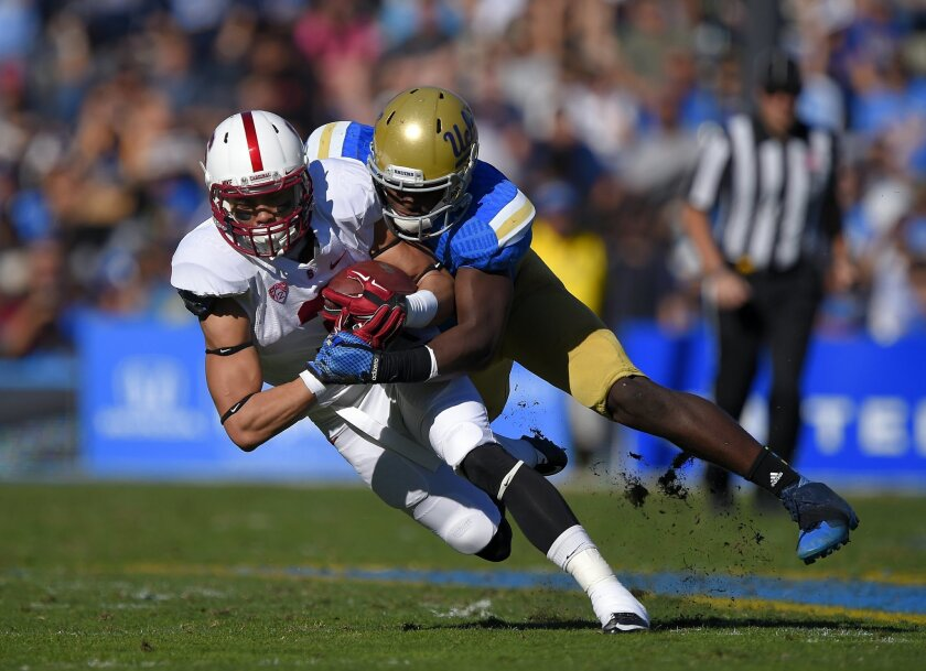 FILE - In this Nov. 28, 2014, file photo, Stanford wide receiver Michael Rector, left, is tackled by UCLA linebacker Myles Jack during the first half of an NCAA college football game in Pasadena, Calif. The UCLA Bruins feel they're still searching for national respect even after two straight 10-win
