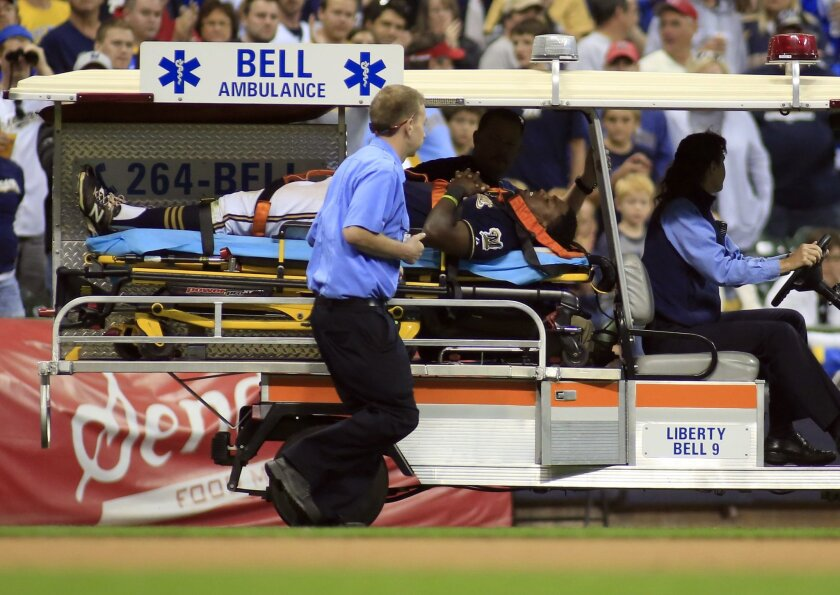 Milwaukee Brewers third baseman Elian Herrera is carted off the field after colliding with left fielder Shane Peterson while trying to catch a ball hit by Cincinnati Reds' Skip Schumaker during the eighth inning of a baseball game Saturday, Sept. 19, 2015, in Milwaukee. (AP Photo/Darren Hauck)