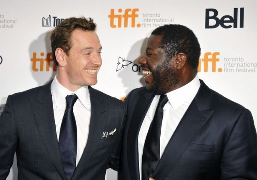 """Michael Fassbender is all smiles at the Toronto Film Festival with """"12 Years a Slave"""" director Steve McQueen."""