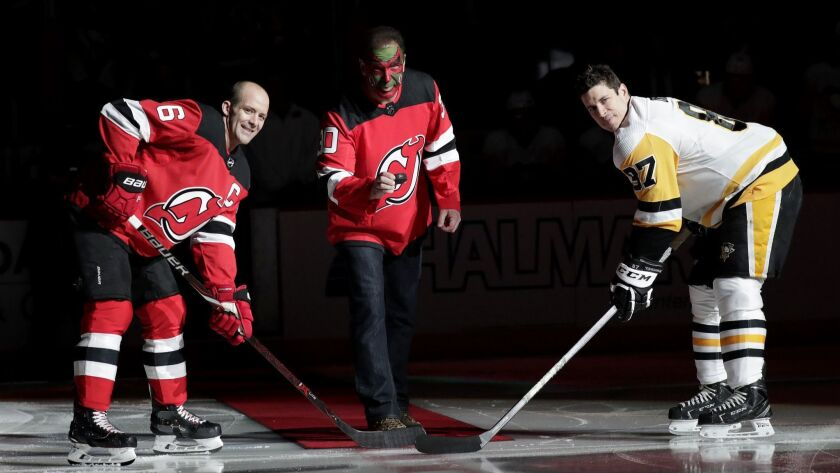 """Patrick Warburton, reprising his David Puddy role from """"Seinfeld,"""" prepares to drop the ceremonial first puck for Andy Greene of the Devils, left, and Sidney Crosby of the Penguins."""