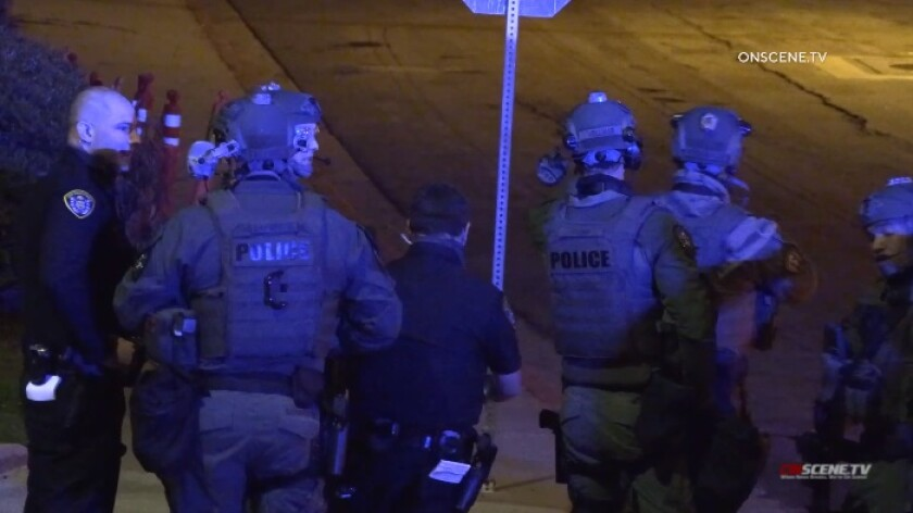 SWAT officers gather on a street corner near San Diego High School, where a wanted man was holed up in a trash bin.