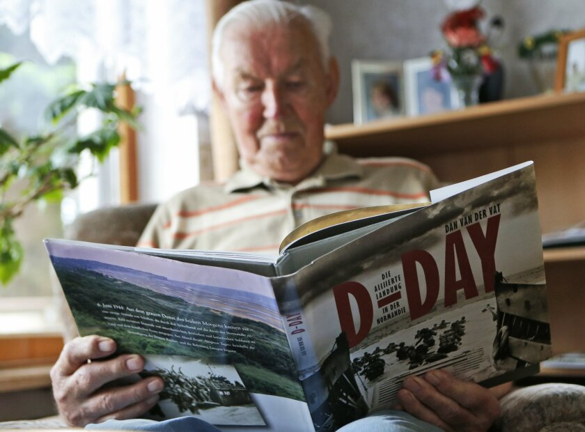 In this file picture taken May 28,2014, Germany' s World War 2 and D-Day veteran Paul Golz reads in a book during an interview with the Associated Press in his hometown Koenigswinter, Germany. Paul Golz, one of a few German veterans who plans to attend this week's events marking the 70th anniversary of the D-Day invasion, recalls the generosity of an Allied soldier in Normandy and his luck at being taken prisoner by Americans instead of being sent to fight on the eastern front. (AP Photo/Frank Augstein)
