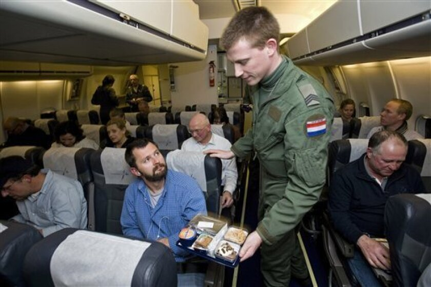 FILE - This Feb. 22, 2011 file photo released by Dutch Defense Ministry shows a Dutch soldier serving food to passengers aboard a Dutch military plane after being evacuated from Tripoli's airport in Libya. The Dutch government says Friday, April 8, 2011, it will release details of its plan to cut 10,000 military jobs, or about one in seven military personnel, one of the most dramatic displays of the Cabinet's determination to balance the Netherlands' budget by 2015. (AP Photo/ Dutch Defense Ministry, File)