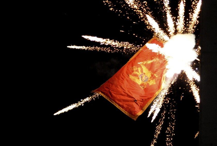 The Montenegrin flag flying from the Montenegrin Embassy, is targeted with fireworks by Serbian ultra-nationalists during a protest against a religion rights law adopted by Montenegro's parliament last month, during a mass protest in Belgrade, Serbia, Thursday, Jan. 2, 2020. Montenegro on Friday strongly denounced aggression against its embassy in Serbia during a protest by some thousands of ultra-nationalists, saying the action represented an attack on the country's independence. (AP Photo/Ana Paunkovic)