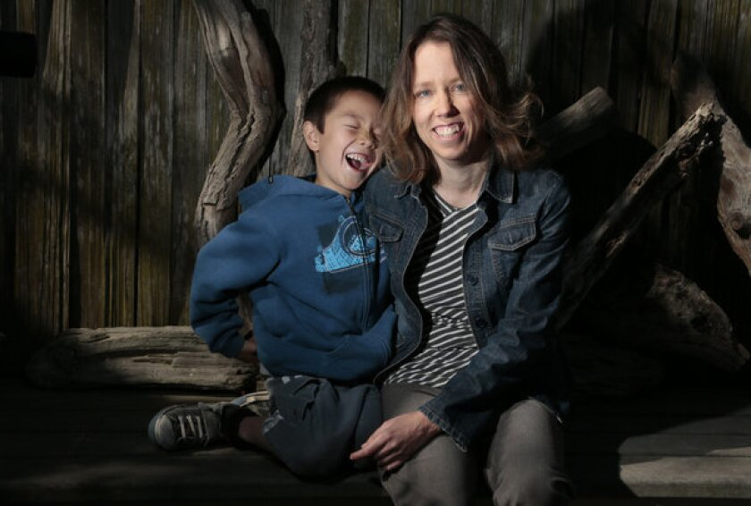 Tara Sievers -- shown at her Belmont Shores home with her 7-year-old son, Bodhi -- is one of an uncertain number of workers whose hours are being cut to avoid the 2010 healthcare law's requirement that employers provide insurance to all full-time staffers.