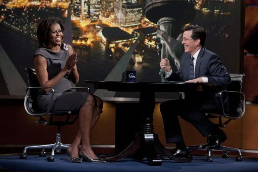 "In this photo provided by Comedy Central, first lady Michelle Obama laughs with Stephen Colbert during her appearance on Comedy Central's ""The Colbert Report"" in New York. Obama has been everywhere from a West Point mess hall to a NASCAR speedway in the past year to drum up support for military families through her ""joining forces"" campaign. On Wednesday, she marked the program's one-year anniversary by taking stock of what's been done and challenging Americans to do even more. (AP Photo/Comedy Central, Kristopher Long)"